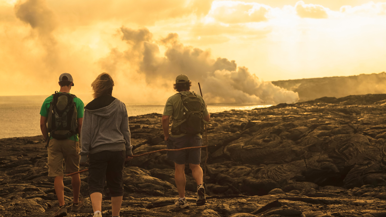 three people walking near solidified lava flow