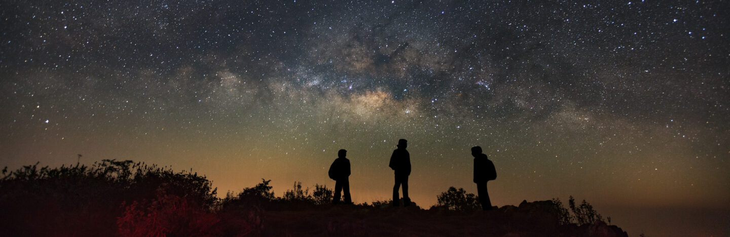 Three people looking at night sky