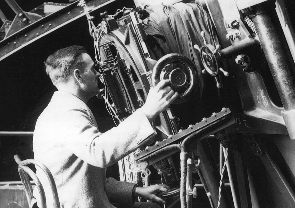 Black and white photo of Edwin Hubble looking into an old telescope