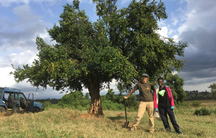 researchers in front of an African arrow poison tree