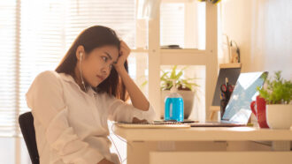 woman looking bored at a laptop