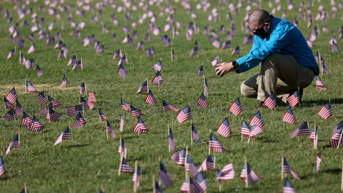 A man wearing a mask crouches down on a lawn covered with many small American flags on it