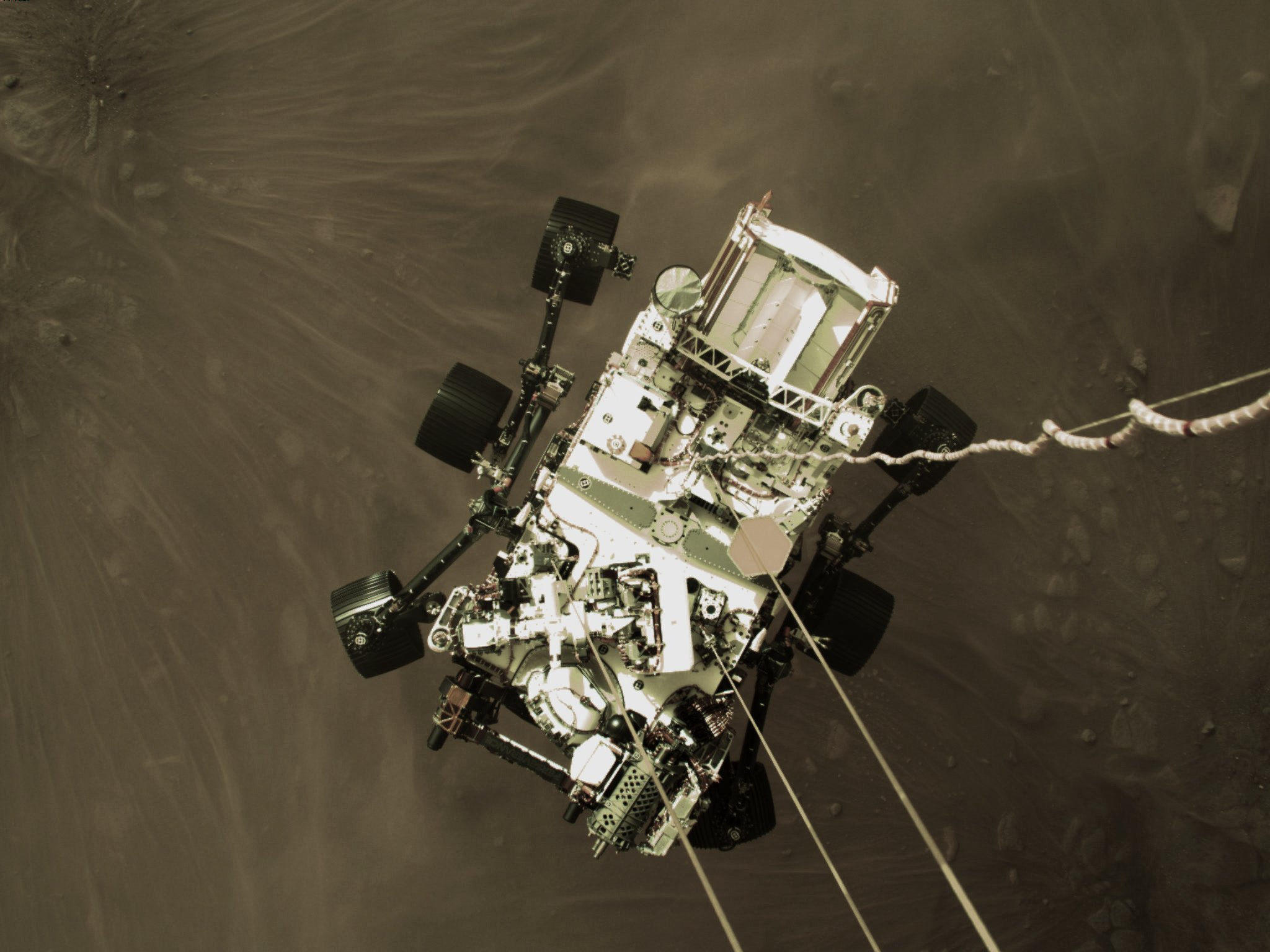 image of rover dangling above Mars surface