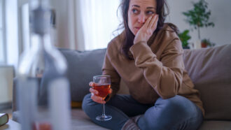 distraught woman sitting on a sofa with a glass of wine