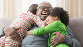 children hugging happy older person