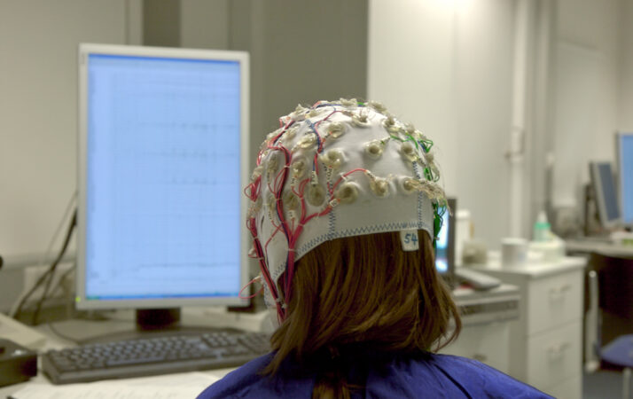 a person seen from behind wearing a white EEG cap