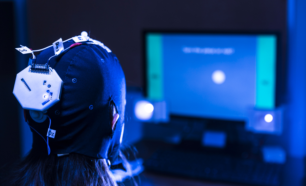 A person wearing a tight-fitting device on her head looks at a computer screen
