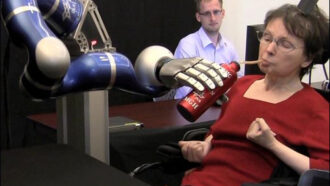 a woman drinks from a water bottle held by a robotic arm