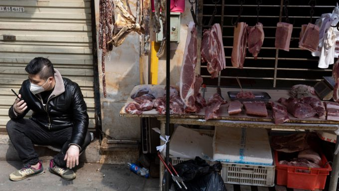 man sitting next to a meat market stand in Wuhan, China
