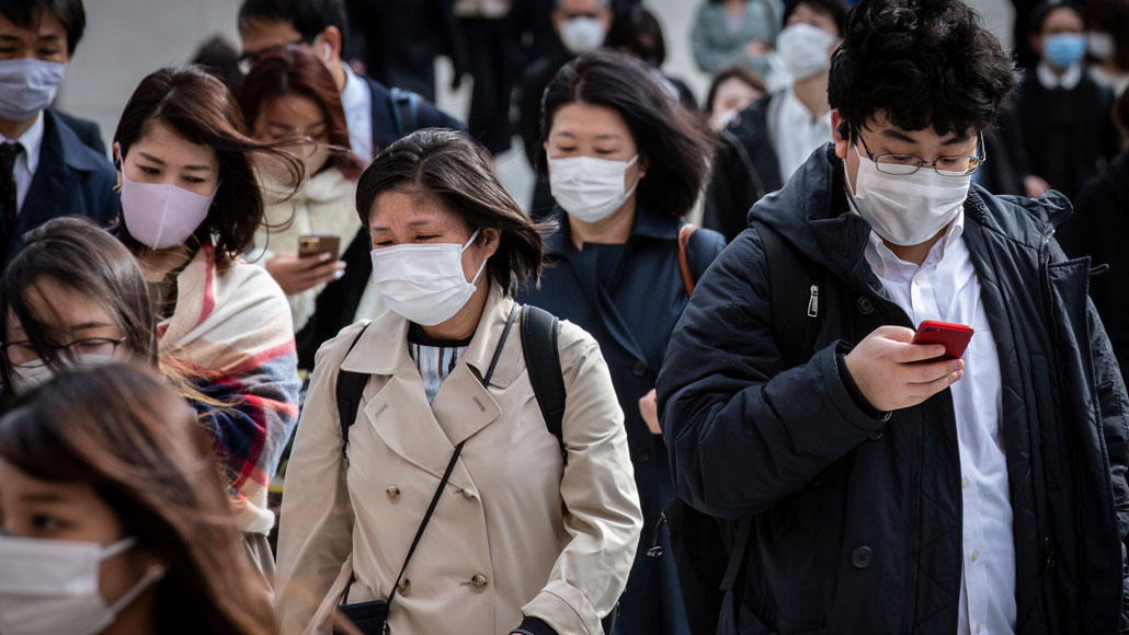 crowd of Japanese commuters wearing masks