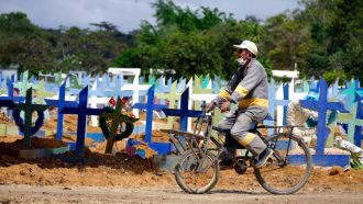 man riding a bicycle in front of cemetery graves in Manaus, Brazil