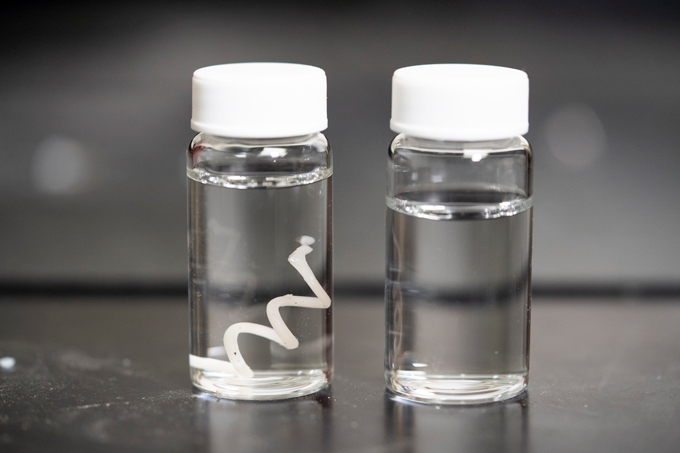 vials of tap water containing new plastic filament before and after degradation
