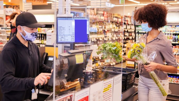 woman wearing a face mask places her groceries on a checkout counter while an employee in a face mask scans them