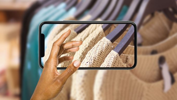 stock art collage of a hand reaching through a phone