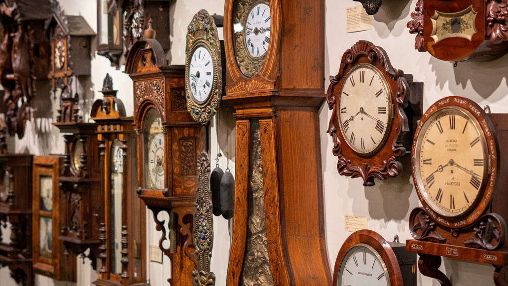a wall of old-fashioned clocks
