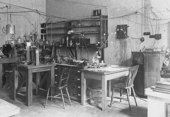 old black and white photo of a lab with wooden desks and shelves