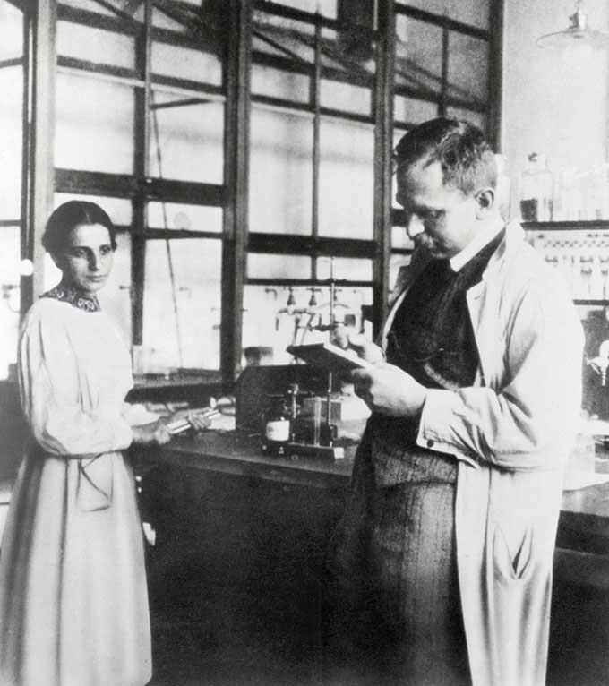 Lise Meitner is next to a lab table and Otto Hahn holds a clipboard