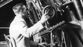 black and white photograph of Edwin Hubble looking into a telescope