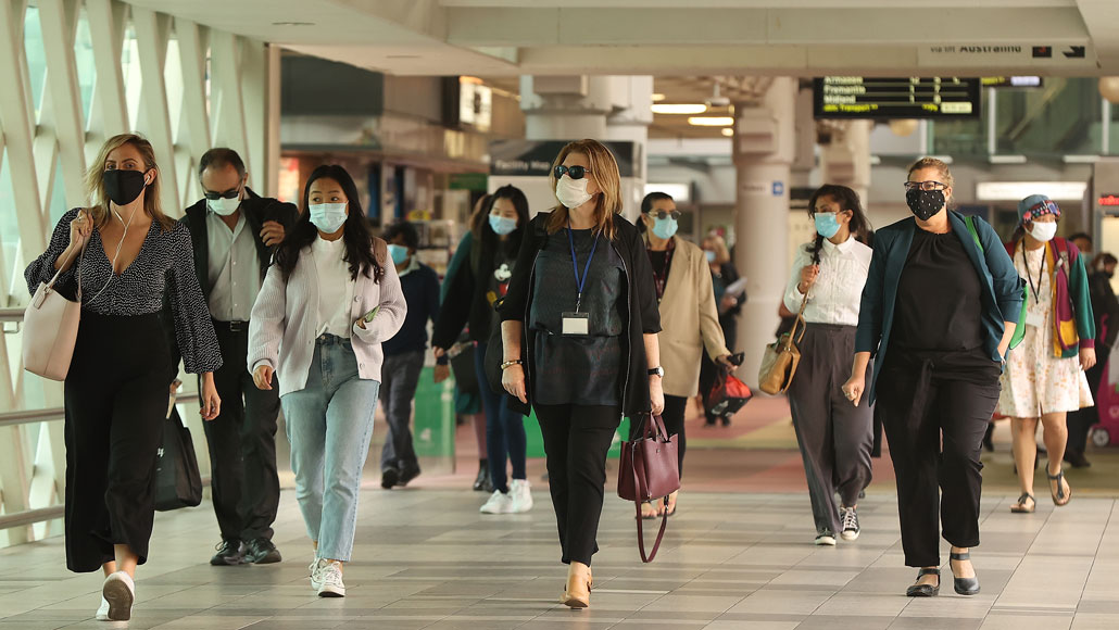 masked people walking in a train station overpass tunnel