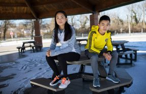 a 14-year-old girl and 12-year-old boy sitting on a picnic table