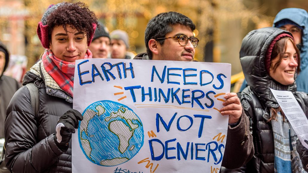 """People hold up a poster that reads, """"Earth needs thinkers not deniers"""""""