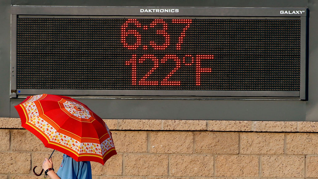 person walking by an electronic sign in Phoenix that reads 122 degrees and 6:27pm