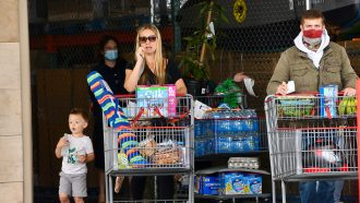 woman and child at grocery store not wearing masks with man wearing mask