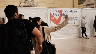 photo of six or so people in Grand Central Station wearing facemasks. a woman in the center takes a selfie