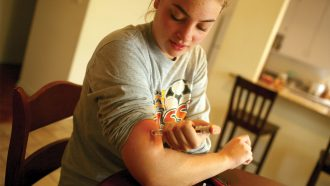 A young woman sitting at a kitchen table injects insulin into her arm