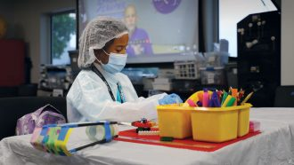 a kid in a clean room suit wearing gloves a mask and head covering playing with lego blocks