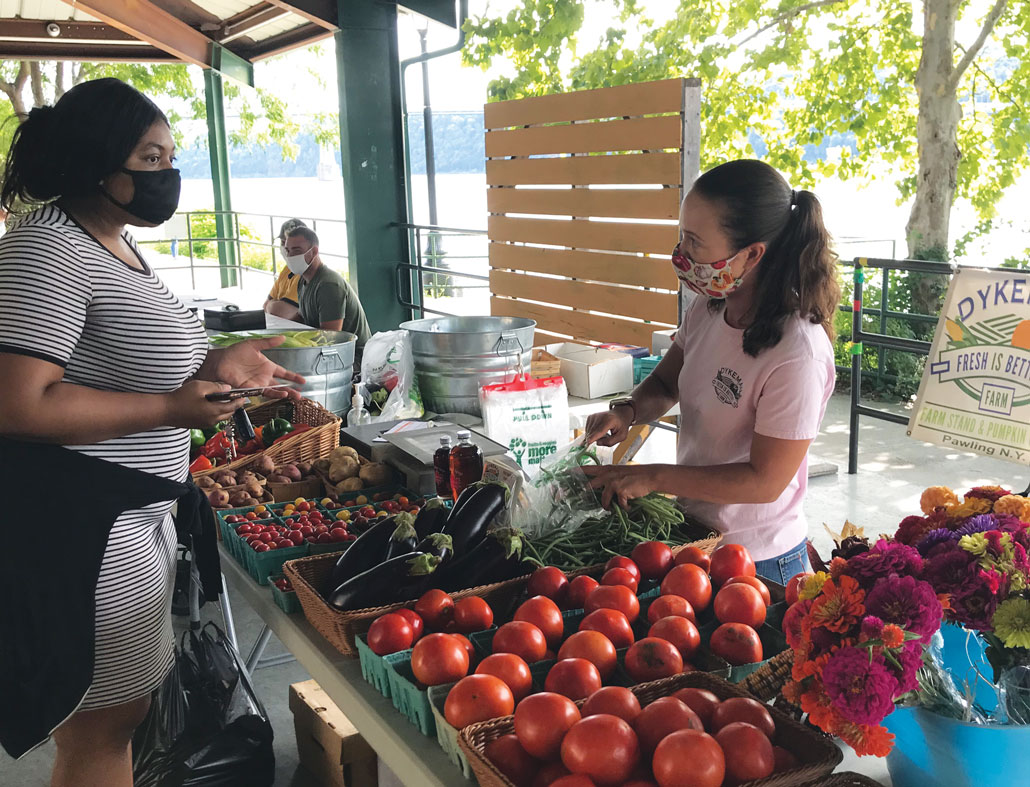 a photo of people at a farmer's market, everyone is wearing face masks