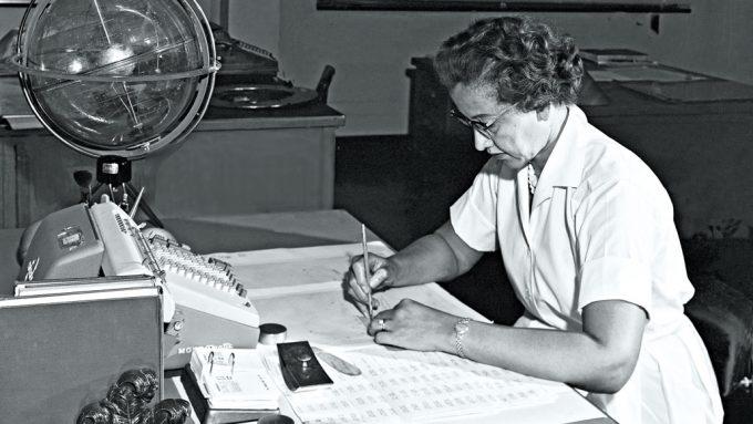 black and white photo of Katherine Johnson sitting at a desk