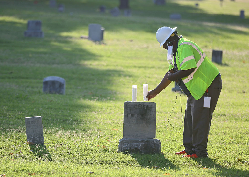 Kavin Ross places candles on Eddie Lockard's headstone