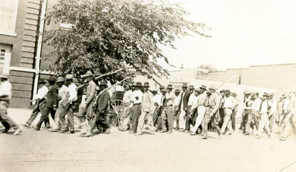 black and white image of National Guardsmen with rifles marching Black people to an internment site