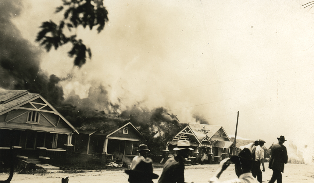 black and white image of craftsman homes on fire with white vigilantes in the foreground