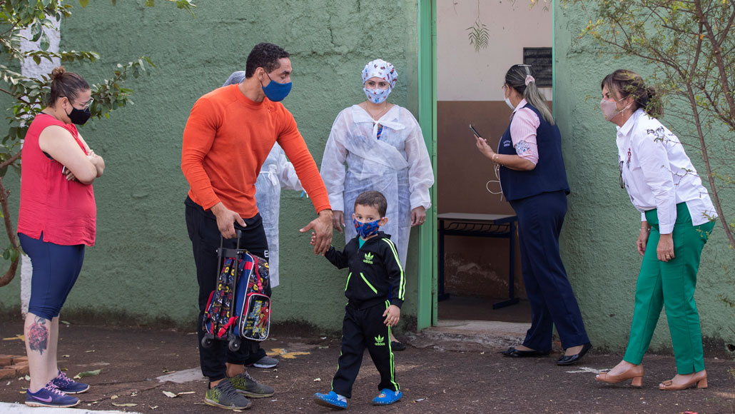 A man and woman wearing face masks greet a young boy walking out of a school where four people, also in face masks, are standing in the doorway