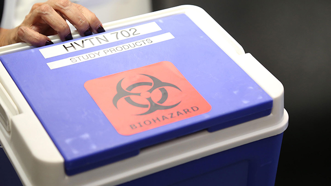 a hand holding the handle of a small blue cooler with a red 'biohazard' sticker on it