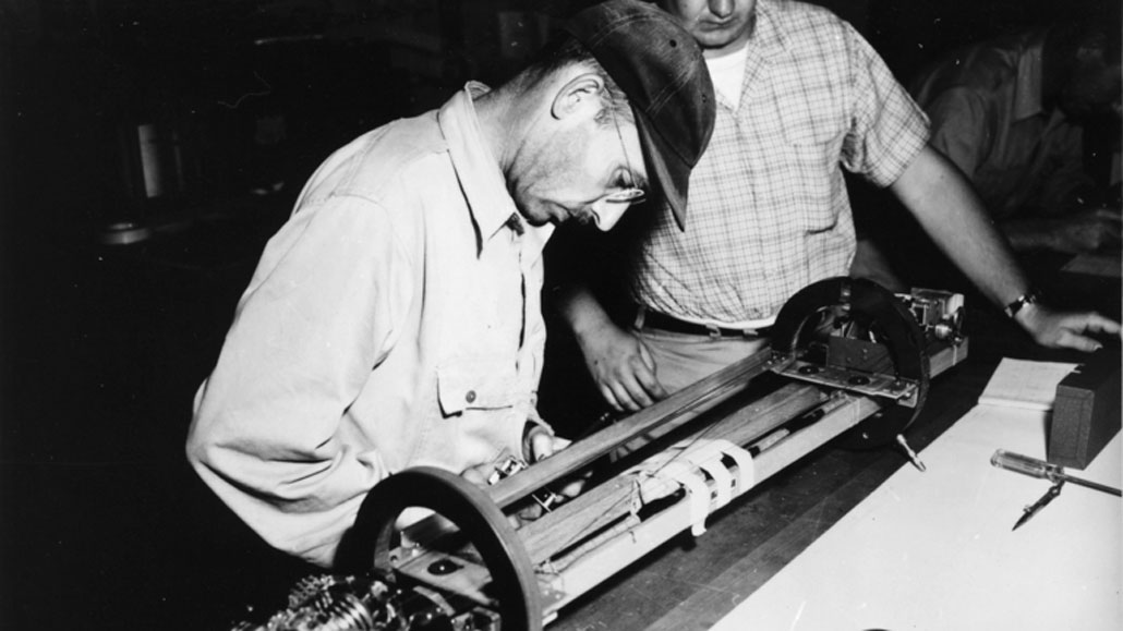 black and white photo of a man in a cap with glasses leaning over a tabletop device while another man looks on