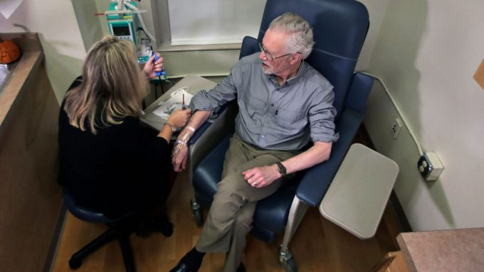 man sitting in a chair receives an infusion of aducanumab