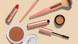 several makeup items - lipstick, a compact, blush brush, mascara - sit on a cream-colored background