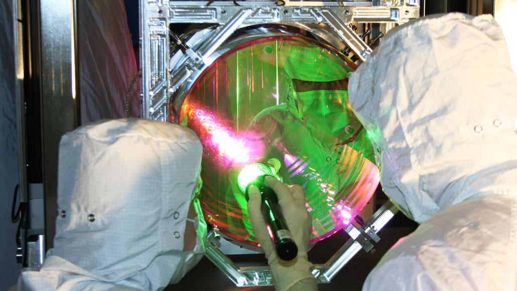 scientists working on a LIGO mirror