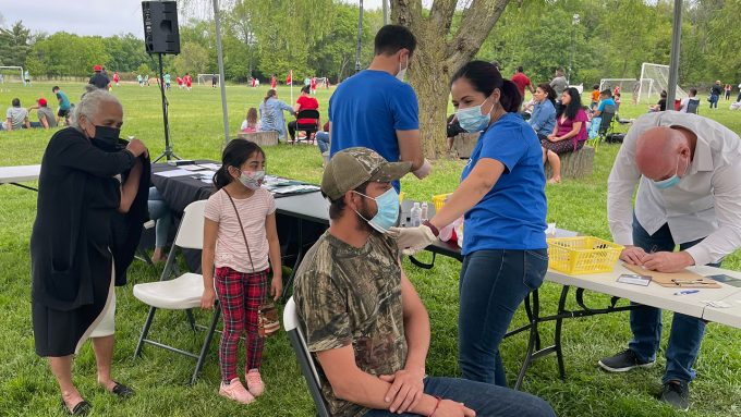 Melissa Pluguez gives a man the COVID-19 vaccine at an outdoor outreach event