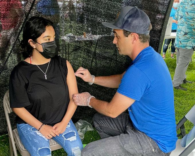 José Torradas rubs alcohol on a masked woman's arm