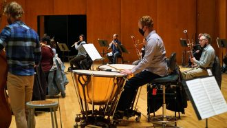 Michael Pape sits behind two timpani drums while others rehearse in the background