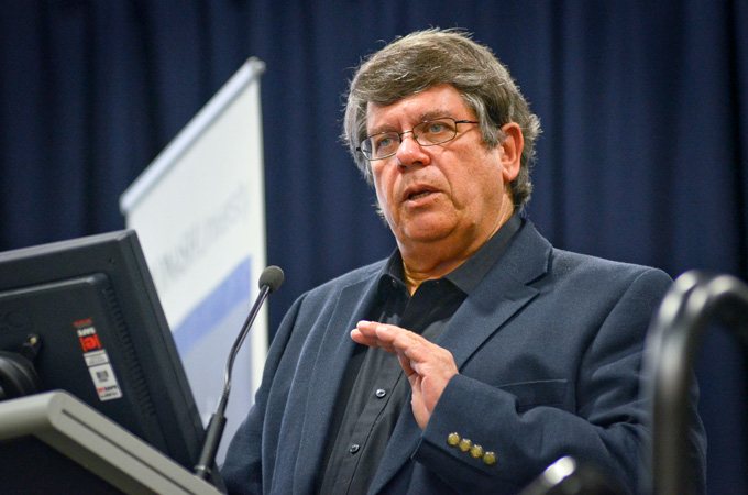 a man with dark hair and glasses wearing a sport coat speaking at a lectern