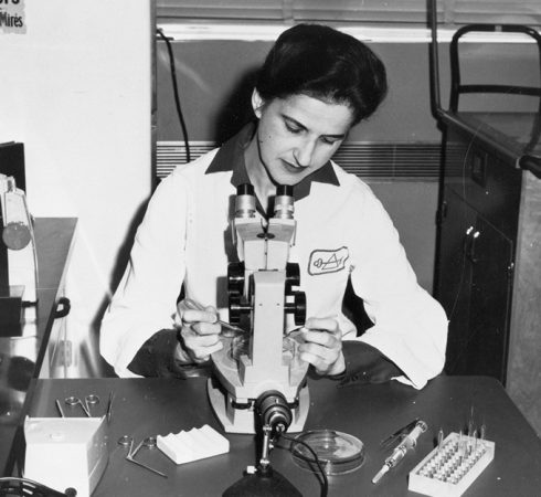 black and white image of Beatrice Mintz looking into a microscope