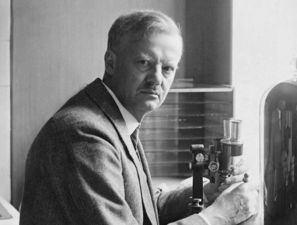 black and white photograph of a man looking at the camera and holding a microscope