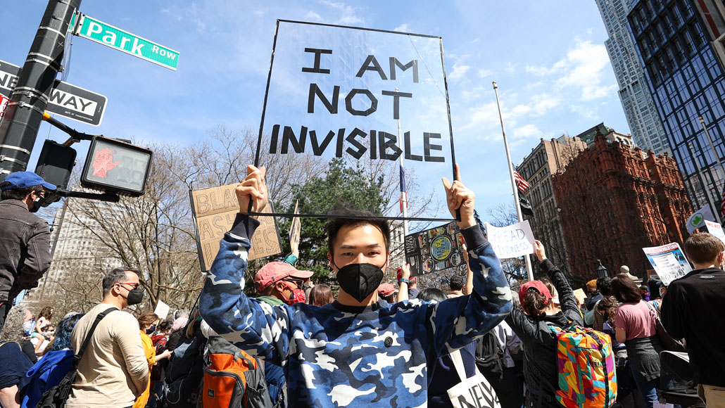 """protester holds a sign that reads """"I am not invisible"""""""
