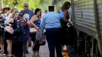a train conductor monitors people boarding a train car
