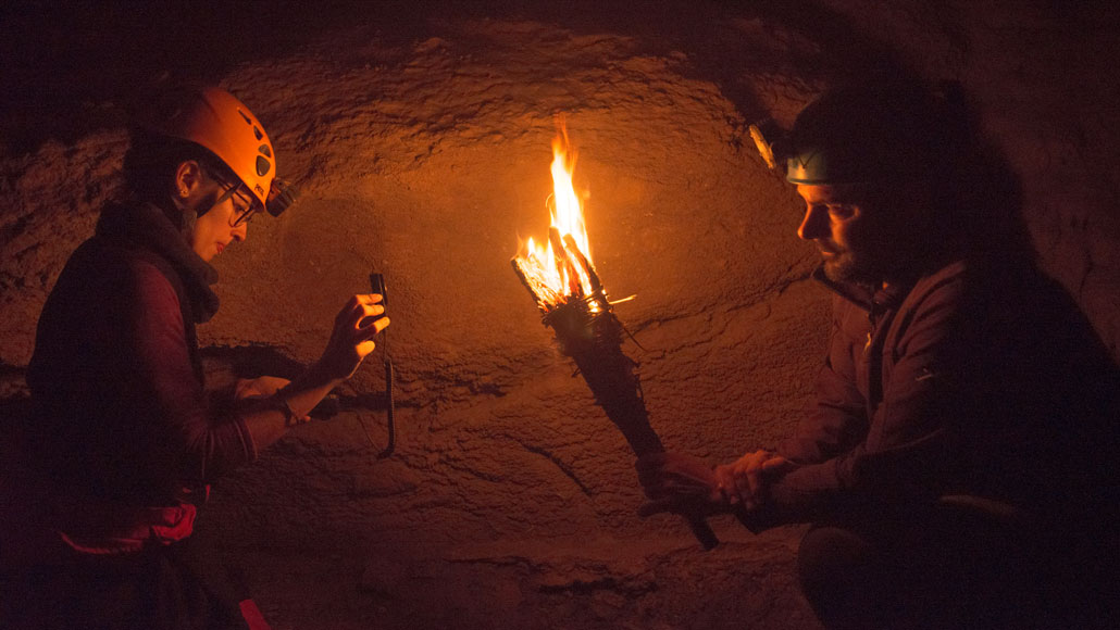 two researchers, one holding a torch in a dark cave